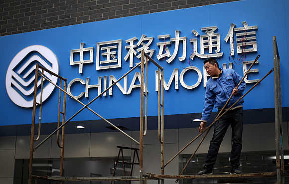 A labourer works in front of a sign for China Mobile at the company's office in downtown Shanghai.