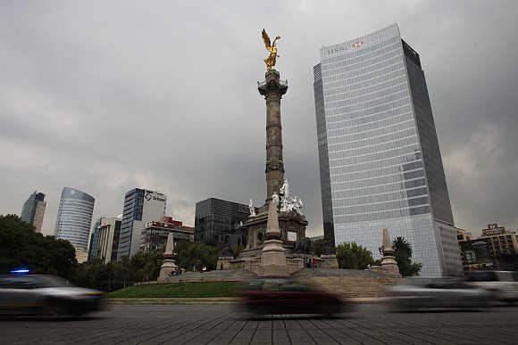 Cars drive past the Angel of Independence monument and British bank HSBC's headquarters in Mexico City.