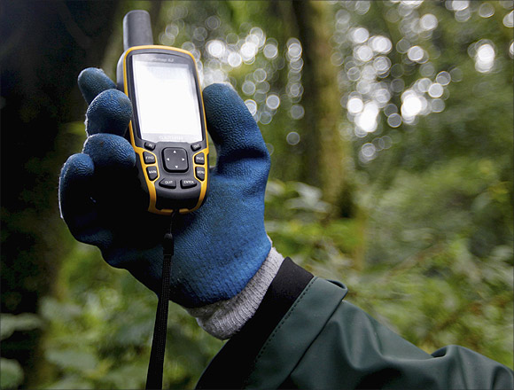 A scientist holds up a GPS device.
