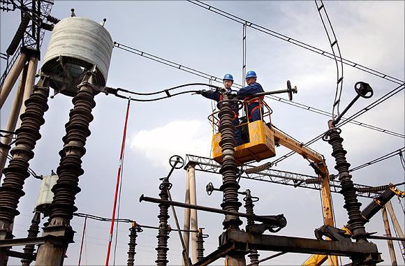 Employees inspect the equipment at an electric power transformation.