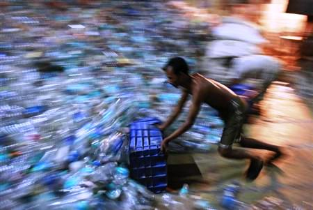 A man collects empty plastic bottles to be recycled at a factory in a slum in