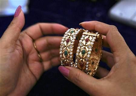 A customer selects one-carat gold bangles during an exhibition in Jammu.