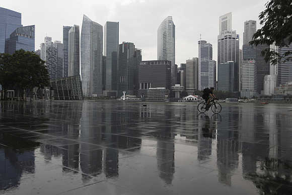 A cyclist rides past the skyline of the Central Business District in Singapore.