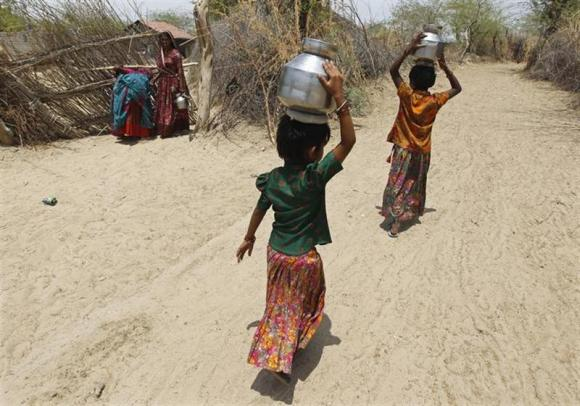 Village girls carry metal pitchers filled with water supplied by the government in Gujarat.