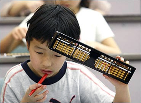 An elementary school boy holds a Japanese traditional calculating tool called the soroban (abacus).