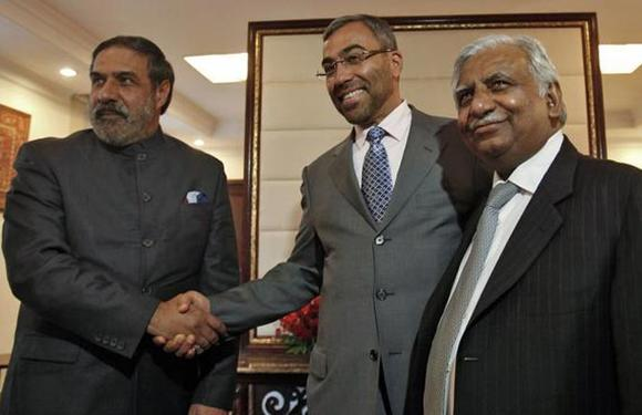 India's Trade Minister Anand Sharma shakes hands with Ahmed Ali-al-Sayegh, a board member of Abu Dhabi's Etihad Airways, as Jet Airways Chairman Naresh Goyal (L-R) looks on.