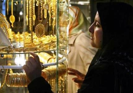 A Palestinian woman looks at gold jewellery at the traditional gold market, where people buy as well as sell gold, in Gaza City.