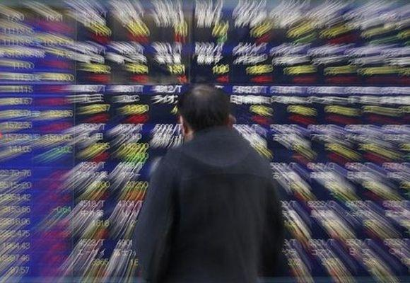A man looks at a stock index board outside a brokerage in Tokyo.