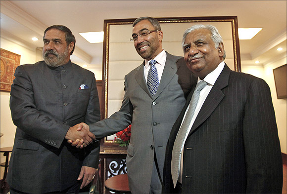 Trade Minister Anand Sharma shakes hands with Ahmed Ali-al-Sayegh, a board member of Abu Dhabi's Etihad Airways, as Jet Airways Chairman Naresh Goyal (L-R) looks on.