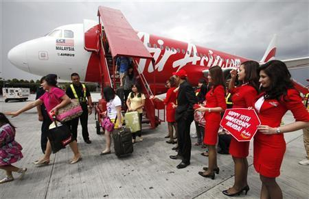 AirAsia staff greet passengers arriving from Kota Kinabalu to the Low Cost Carrier Terminal in Sepang outside Kuala Lumpur.