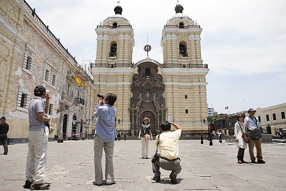 Tourists take pictures of the San Francisco Monastery in Lima, Peru.