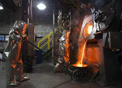 Workers wearing heatproof overalls pour molten gold from a crucible into moulds in a workshop at Kumtor gold mine extraction factory.