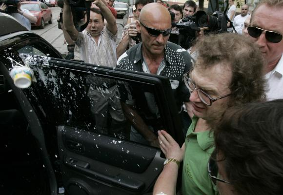 Sour cream is thrown at Sergey Mavrodi (in green shirt), former head of a collapsed 1990s investment scheme, as he gets into a car after leaving prison in Moscow.