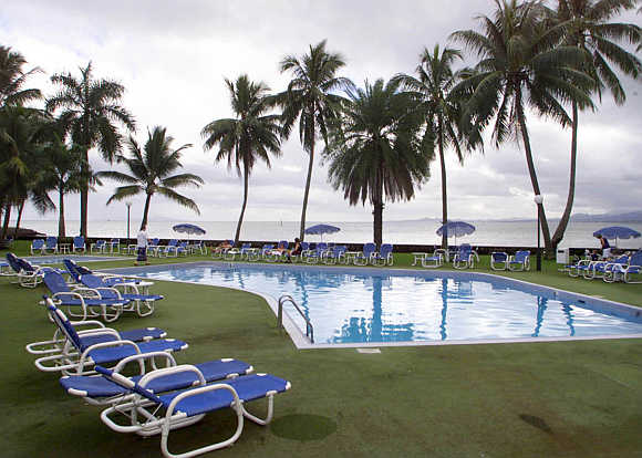 A woman walks around a swimming pool at an international hotel in Suva, Fiji.