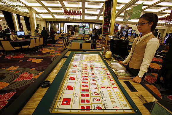 A croupier stands in front of a gaming table inside a casino in Macau.