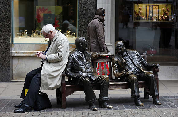A man looks at his mobile phone while perched on the side of a sculpture entitled 'Allies' by Lawrence Holofcener on New Bond Street in London.