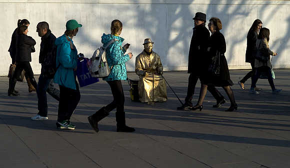 Tourists walk past a street performance artist on the south bank in London.