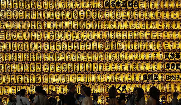 People walk in front of paper lanterns during the Mitama Festival at the Yasukuni Shrine in Tokyo. More than 30,000 lanterns light up the precincts of the shrine, where more than 2.4 million war dead are enshrined.