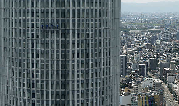 Workers clean the windows of a high rise building at the Nagoya station in Nagoya, central Japan.