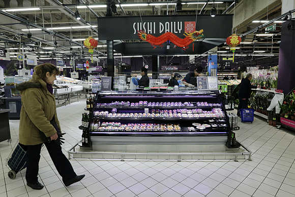 A customer walks past Sushi daily bar foods section at Carrefour's Bercy hypermarket in Charenton, a Paris suburb.