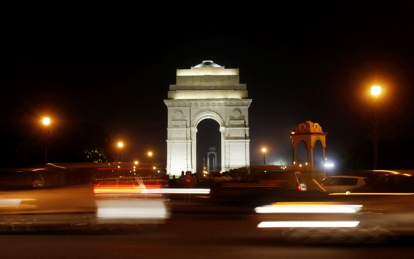 Heavy traffic moves in front of the India Gate before Earth Hour in New Delhi March 23, 2013.