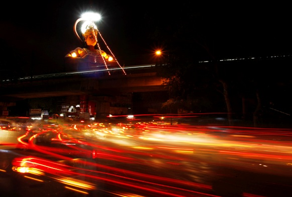 Traffic moves near a statue of Hindu monkey god Lord Hanuman in a street in New Delhi.