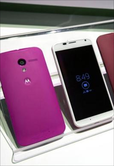 Different colored examples of Motorola's new Moto X phones rest on a table at a launch event in New York.