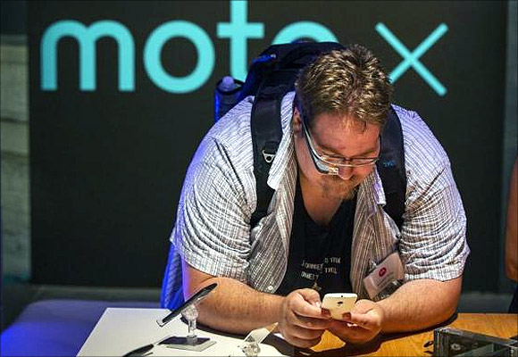 A man using Google Glass examines one of Motorola's new Moto X phones.