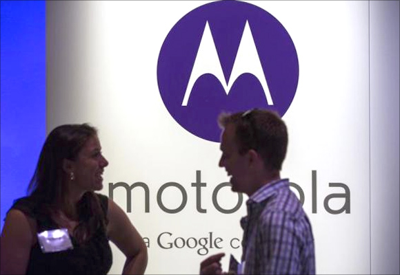 A man and woman laugh in front of a Motorola logo at a launch event for Motorola's new Moto X phone in New York.
