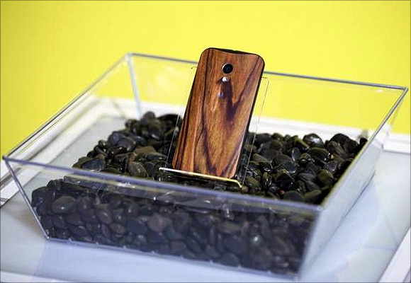 A phone with a wooden back on it rests in a display.