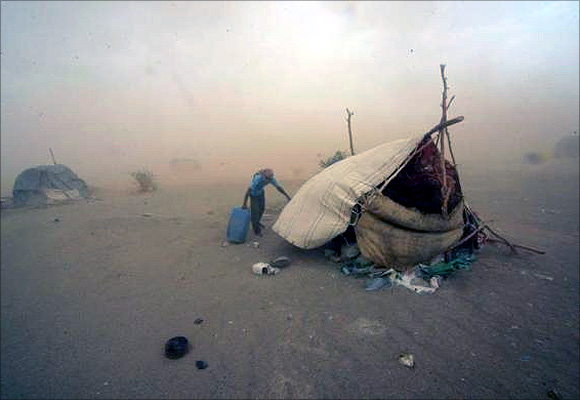 Gold mine workers walk to their shelter during a sandstorm in Al-Ibedia locality at River Nile State.