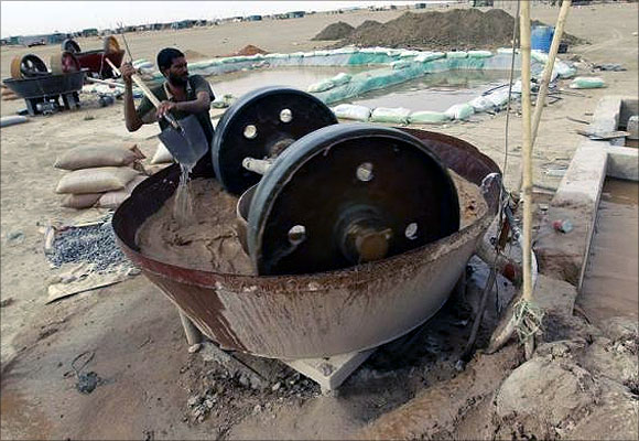 A gold mine worker uses a gold crusher at a local mine in Al-Ibedia locality at River Nile State.