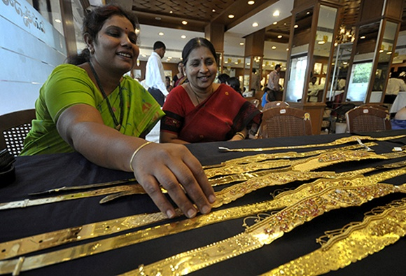 A woman checks a gold waist belt inside a jewellery shop in Hyderabad.
