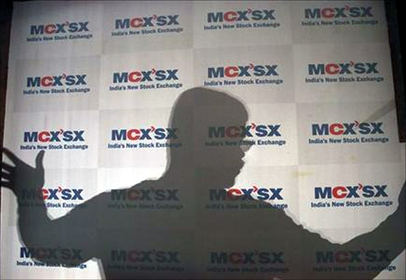 A man moves an advertising poster bearing the MCX-SX logo at their Exchange Square building in Mumbai.