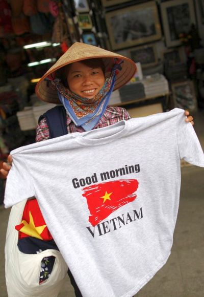 A street vendor shows a T-shirt for sale in the old quarter of Hanoi.