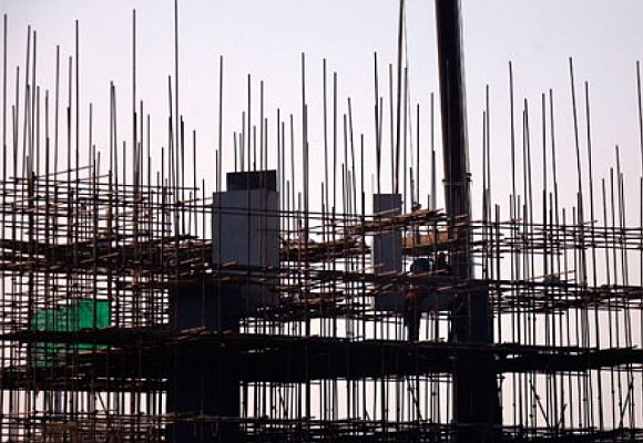 Workmen stand on scaffolding as they work on the construction of a building.