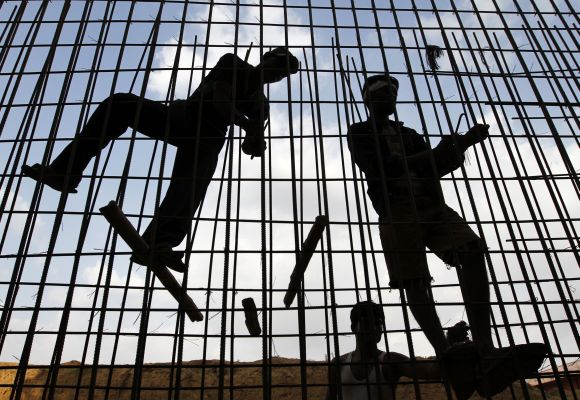 Labourers fasten iron rods together at the construction site.