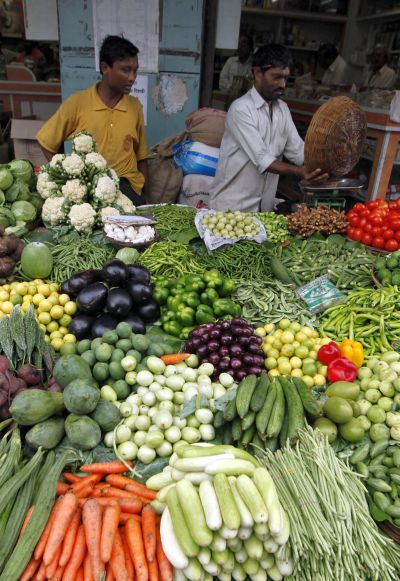 A vendor sells vegetables at a market in Mumbai.