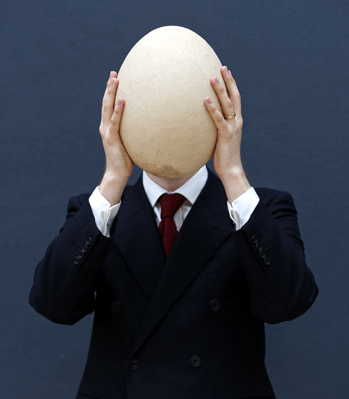 Christie's specialist James Hyslop holds a pre-17th century, sub-fossilised Elephant Bird egg in London.
