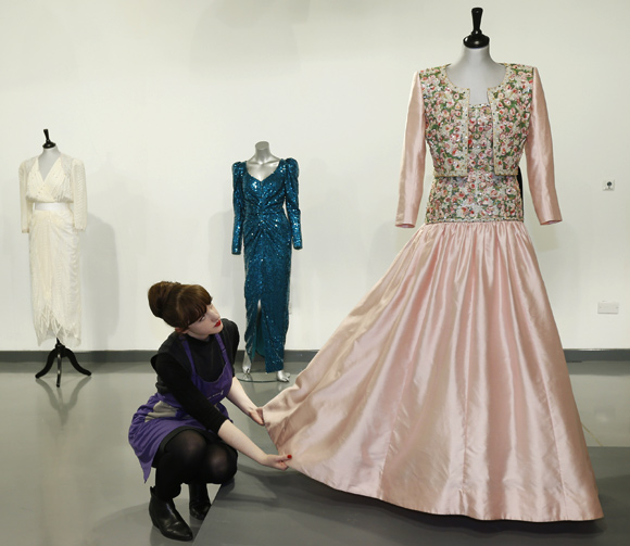 House assistant Lucy Bishop poses with a Catherine Walker Mughal-inspired pink slubbed silk evening gown and bolero worn by Diana, Princess of Wales, at Kerry Taylor Auctions in London.