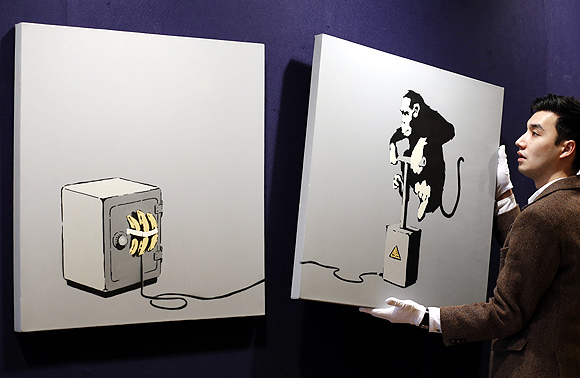 A gallery assistant poses for photographers with British street artist Bansky's diptych work Monkey Detonator at Bonhams auction house in central London.