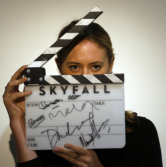 A worker holds a clapperboard from the film Skyfall during a media preview of 50 Years of James Bond - the Auction, at Christie's in London.