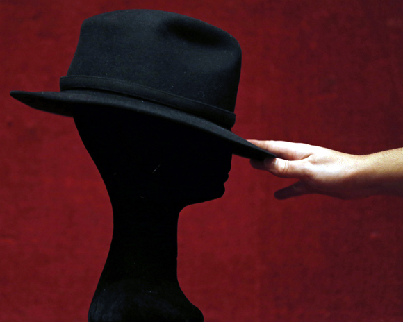 An assistant displays a black Fedora hat owned by late singer Michael Jackson at Drouot auction house in Paris.