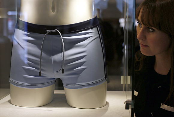 A employee poses next to a pair of swimming trunks, worn by Daniel Craig in the film Casino Royal, during a media preview of 50 Years of James Bond - the Auction, at Christie's in London.