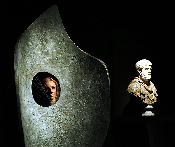 A Christie's employee poses with artworks by Barbara Hepworth Curved Form (L) and one of a pair of polychrome marble busts at Christie's auction house in London.