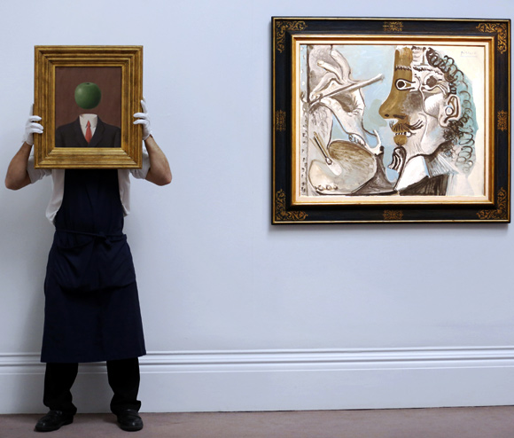 A Sotheby's employee poses with Rene Magritte's artwork L'idee (L) alongside Pablo Picasso's picture Le Peitnre at Sotheby's auction house in London.