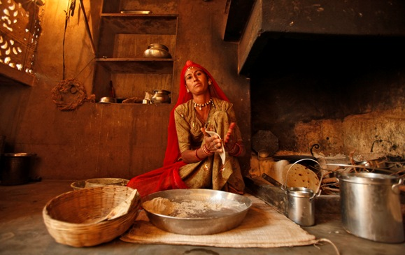 Laxmi, 34, who works as a construction labourer, prepares a roti inside her house at Merta district in Rajasthan.