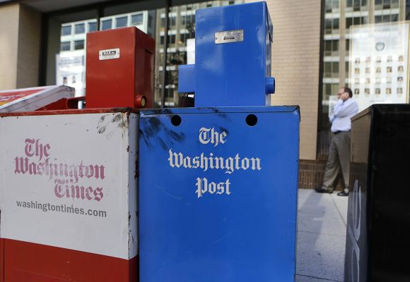 Washington Post (R) and Washington Times newspaper boxes are pictured outside the entrance to the Washington Post headquarters in Washington
