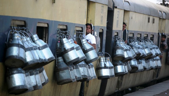 Milk containers hang from the windows of a passenger train in Ghaziabad on the outskirts of New Delhi.