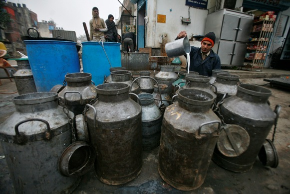 A milkman pours milk into a container to deliver to shops in Noida, Uttar Pradesh.